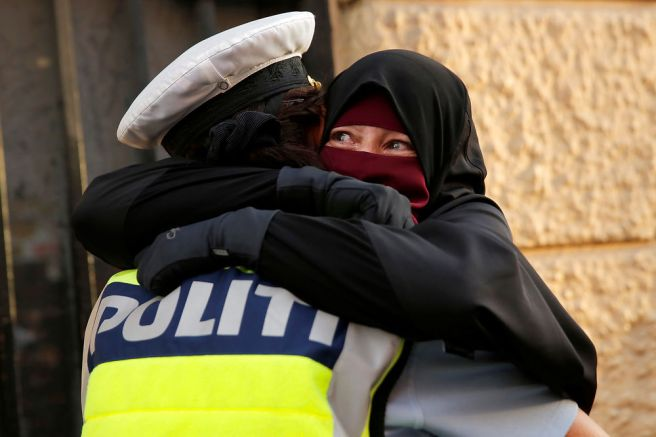 Ayah, a wearer of the niqab weeps as she is embraced by a police officer during a demonstration against the Danish face veil ban in Copenhagen